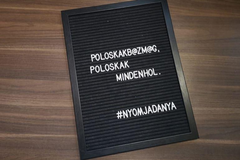 """A képen egy tábla látható, rajta """"Poloskákb@zmeg, polsokák mindenhol."""" felirattal."""